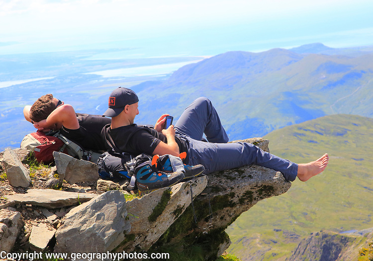 Two male walkers resting on rock overhang, Mount Snowdon, Gwynedd, Snowdonia, north Wales, UK
