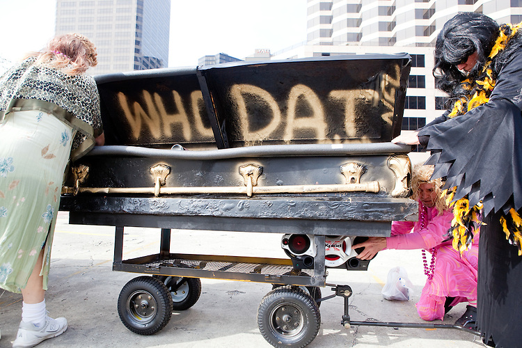 (From L) Rodney Crout, Rodney Parent, and Michael Landeche prepare a funeral casket outfitted for the parade in Buddy D's honor on January 31, 2010 in New Orleans.<br /> <br /> Thousands of Saints fans wearing dresses paraded from the Louisiana Superdome to the French Quarter to honor a promise made by the late sportscaster and Saints super-fan Buddy Diliberto aka &quot;Buddy D&quot;.<br /> <br /> In 1993 Buddy D, who passed away in 2005, remarked on air that if the Saints were to make it to the Super Bowl, he would wear a dress and dance down the streets.  The comment was repeated at various times and never forgotten by his listeners.<br /> <br /> Led by former New Orleans Saints quarterback Bobby Hebert, who has taken Buddy D's place on WWL radio, thousands made good on his promise for him, dancing, drinking, and cavorting their way down the street, alternately yelling out &quot;Who Dat!&quot; and &quot;Buddy D!&quot; in front of an onlooking crowd an estimated 85,000 people strong.<br /> <br /> The hard luck NFL team the New Orleans Saints has reached its first Super Bowl in team history, after 43 years largely filled with losing seasons and futility.  It is difficult to travel anywhere in the area without some reminder of this fact, as the team and city are intertwined perhaps like no other sports franchise in this country.
