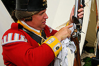 Lance Corporal of the Tenth Regiment of Foot cleans his short land pattern flintlock musket during a re-enactment of the 1775 Siege of Boston, Boston Common, Massachusetts, USA.