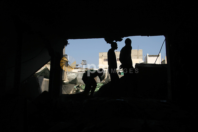 Palestinians inspect damaged buildings following Israeli air strikes on the southern Gaza Strip town of Rafah on November 20, 2012. The Israeli military said it attacked about 100 targets in the coastal strip during the night, using aircraft, warships and artillery. Photo by Eyad Al Baba