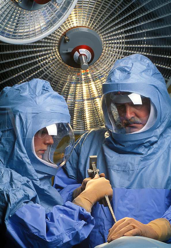 Orthopaedic surgeon in protective surgical suits used to avoid infection during joint replacement surgery (hip , knee)