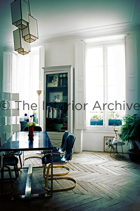 A retro style dining table and chairs in a dining room contrast with the traditional features of the room such as the window shutters and high corniced ceiling.