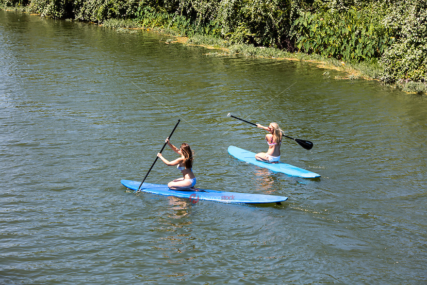 Austin young attractive females relaxing on SUP stand up paddling board on Lady Bird Lake in Austin, Texas.