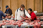 A vendor and customer examine the goods at the game market in Nuuk, Greenland.