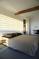 One of the simple bedrooms situated on the upper floor of the converted barn where an original beam supports the ceiling