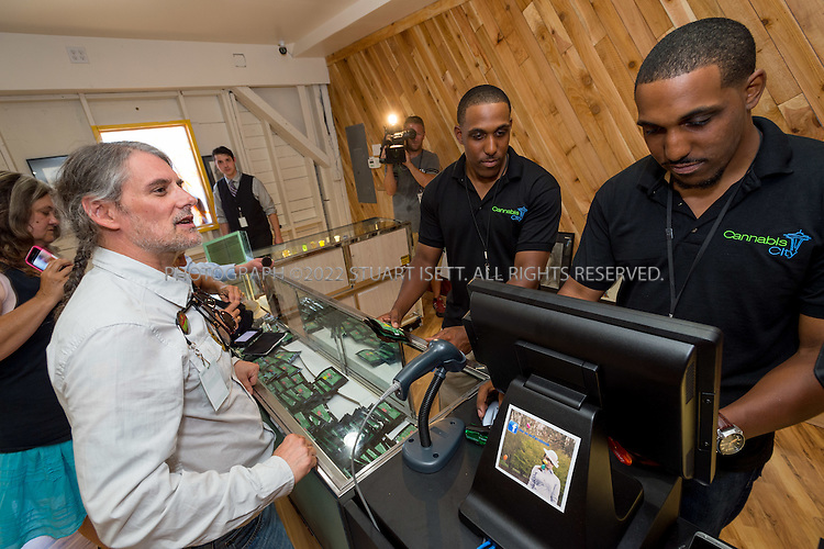 7/8/2014 &mdash; Seattle, Washington<br /> <br /> Customer Vivian McPeak, 55, pays for his legal marijuana<br /> on sale at Cannabis City in Seattle, WASH.<br /> <br /> Cannabis City, owned by James Lathrop, opened today in Seattle, WASH. one of several legal marijauna retail stores to open across Washington State on July 8th, 2014. Of Washington's 334 marijuana license lottery winners, the Washington State Liquor Control Board issued 24 actual retail licenses for the July 8th deadline.<br /> <br /> Cannabis City expected to have 10 pounds of marijuana stocked for their grand opening, selling for $15 to $20 per gram. Because of timing, many retail pot stores in Washington State will face shortages as legal growing operations ramp up production to meet demand. Lines started forming at Cannibis City the night before it opened.<br /> <br /> Photograph by Stuart Isett<br /> &copy;2014 Stuart Isett. All rights reserved.