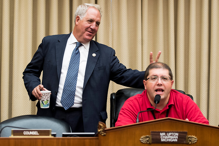 UNITED STATES - OCTOBER 12: Rep. John Shimkus, R-Ill., holds up bunny ear fingers behind a a technician testing the microphones before the start of the House Energy and Commerce Committee hearing on Thursday, Oct. 12, 2017. (Photo By Bill Clark/CQ Roll Call)