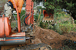 Mini-excavator machine being used to repair a water main break in Atlanta.