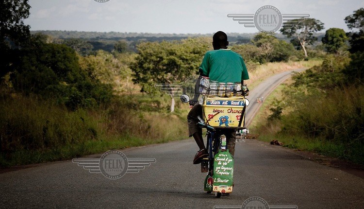 A vendor with his medicines strapped to his bike, rides down the road near Bossembele.