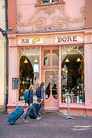 Two women with their luggage traveling in Colmar, France, exploring the colorful old city, stopped outside a cafe.