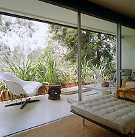 Through a series of sliding glass doors the living room opens straight onto a shady furnished veranda