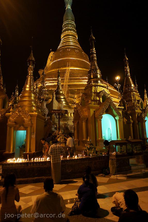 Shwedagon pagoda  at night, worshippers passing by. Yangon, Myanmar, 2011