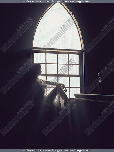 Sunlight lit silhouette of a beautiful young woman sitting on a window sill in a house