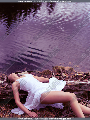 Young unconscious woman in white dress lying on a shore of a lake. Sexual assault, rape victim concept.
