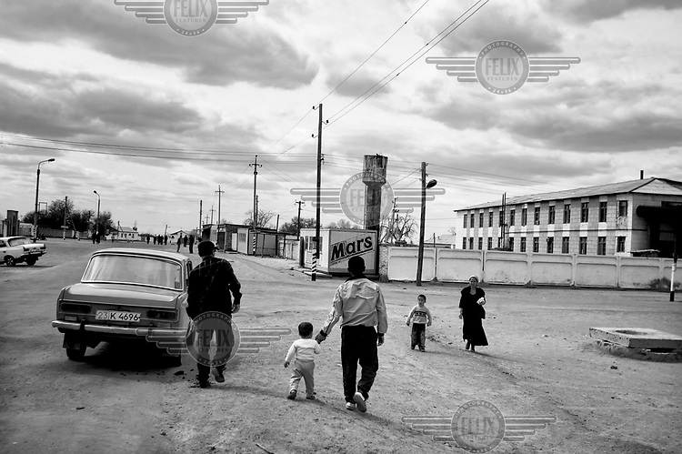 People walking in the town centre. During the 1950s and the 1960s the rivers that feed the Aral Sea (the Amu Darya and the Syr Darya) were diverted for irrigating cotton and other crops. This caused the lake to shrink uncovering sediments heavily polluted with industrial fertilizers that were washed into the lake over the preceding decades. Without the lake's water to contain it these toxic particles were spread by the wind and have caused numerous health problems in surrounding communities. Furthermore, as the lake evaporated the remaining water became increasingly saline and unable to sustain life, destroying the fishing industry. Muynak, once a thriving fishing port, became a depressed and dusty town far from the receding shore.