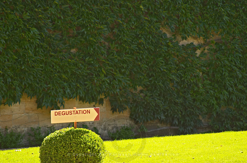 """A sign in the garden pointing to the wine tasting """"degustation"""" at Chateau Cheval Blanc, Saint Emilion, Bordeaux"""