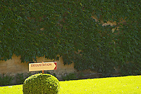 "A sign in the garden pointing to the wine tasting ""degustation"" at Chateau Cheval Blanc, Saint Emilion, Bordeaux"