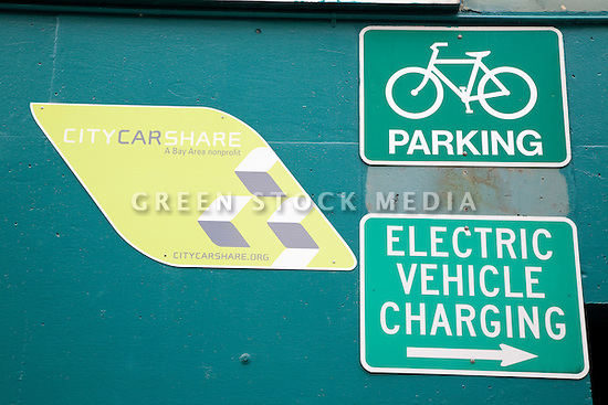 Close Up of City CarShare (car rental service), bicycle parking, and electric vehicle charging station signs on the side of a public parking garage. California, USA