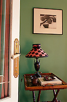 A small bamboo tray table stands against a green wall in the living room