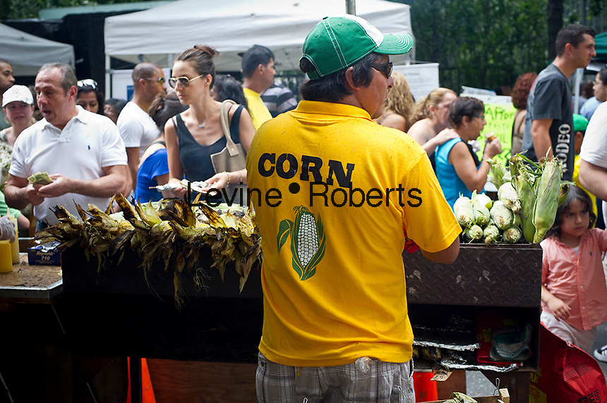 A vendor sells roasted corn at the 28th Annual Brazil Day Festival in New York on Sunday, September 2, 2012.  The festival, which features food, music and other aspects of Brazilian culture, centers around West 46th Street in Midtown Manhattan, known as Little Brazil. (© Frances M. Roberts)