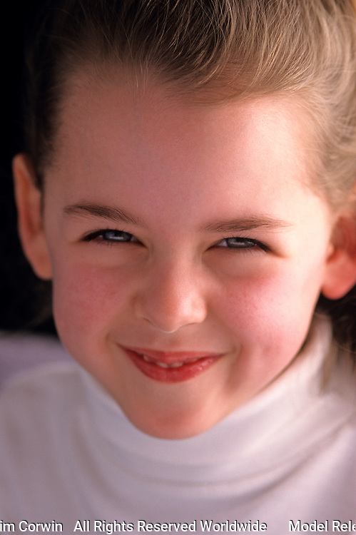 Young girl ( 7 years old) portrait, with mischievous look at camera, Lake Pleasant, Bothell, Washington State USA    MR