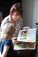 Polish grandma (babcia) reading to her young granddaughter age 63 and 2. Zawady Central Poland