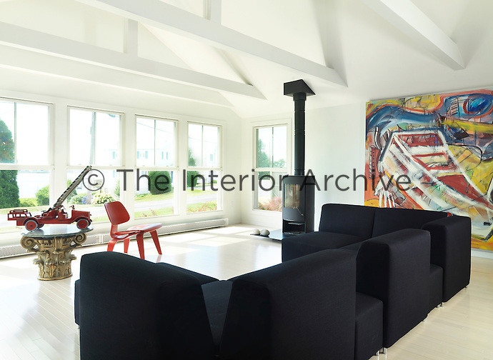 The open-plan living area is flooded with light from a wall of full length windows and is furnished with a large black Tacchini sofa