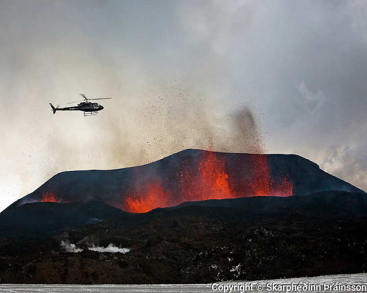 Helecopter over the erupting crater in Fimmvörðuháls, south Iceland in march 2010