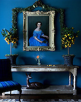 The walls of the entrance hall have been painted a royal blue, echoing the colour of the dress in the gilt-framed portrait which hangs above a rustic table