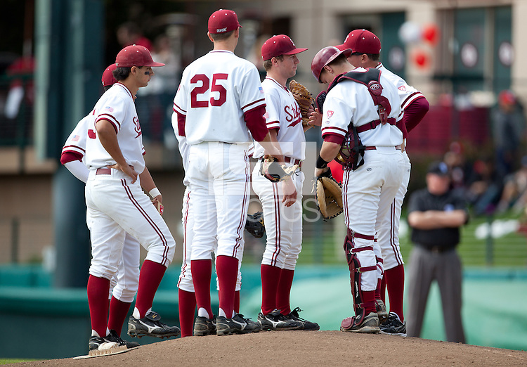 STANFORD, CA - March 27, 2011: Dean McArdle of Stanford baseball meets at the mound with pitching coach Rusty Filter and the infield during Stanford's game against Long Beach State at Sunken Diamond. Stanford won 6-5.