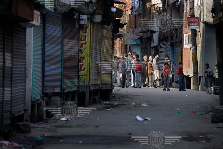 People watch from a side street as paramilitary police enforce a curfew imposed to stop separists gather for a political demonstration in Srinagar, Kashmir, India. © Fredrik Naumann/Felix Features
