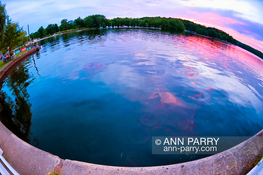 AUG. 25, 2012 - MIDDLEBURY, CONNECTICUT, U.S. - Sunset over Lake Quassipaug, also known as Lake Quassy, in Connecticut, USA, with glimpse of boats and people at far left. Summer sunset panorama taken with 180 degree fisheye lens.