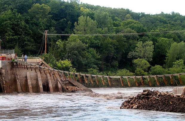 Water rushes through the destroyed dam on Lake Delhi Saturday evening, July 24, 2010.