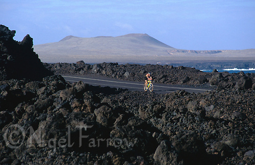MAY 1997 - LANZAROTE, CANARY ISLANDS - .A competitor makes his way through the lava fields of the islands inhospitable landscape during the 1997 Ironman Lanzarote event. (PHOTO (C) NIGEL FARROW)