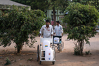 Hospital staff use wheelchairs to carry cans of iJal water from the iJal station at the Medak District Hospital in Medak, Telangana, India.