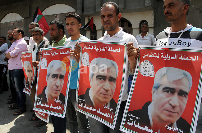 Palestinians holds a picture of the Popular Front Secretary General Ahmad Saadat jailed in Israel, during a protest calling for the release of Saadat, in front of the red cross office in Khan younis in the southern Gaza strip, on June 14, 2015. Photo by Abed Rahim Khatib
