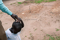 Valente Inziku holds the hand of his daughter Convert Diana in the yard of their homestead in Aribio village, Arua District, Uganda. Valente Inziko's wife Jennifer Anguko and the baby died during childbirth in October 2010 in Arua Hospital. She and the baby are buried in their homestead.