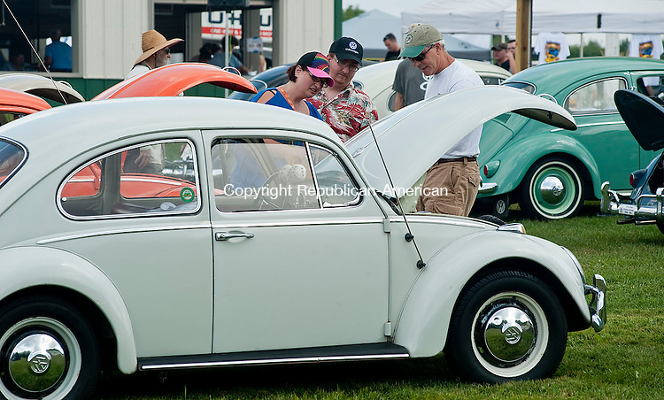 WINSTED, CT-12 AUGUST 2012--081212JS02- Vonda Wood of Wingdale, NY and her son Joshua Wood, center, talks with Fred Stedtler of Mahwah, NJ about his 1967 VW Beetle during the 21st Annual Terryville Lions Club's Bug-A-Fair car show Sunday at the Terryville Fairgrounds. .Jim Shannon Republican-American