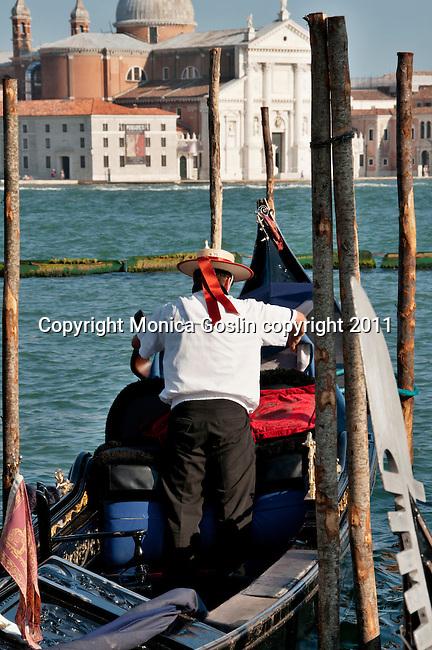 A gondolier docks his gondola in Venice, Italy with the Island of San Giorgi Maggiore in the background