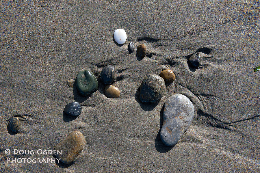 Stones on a beach with the sand eroded from the waves