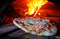 una pizza cuoce nel forno a legna durante   il 14° Campionato mondiale dei Pizzaiuoli   festival della pizza sul lungomare di Napoli