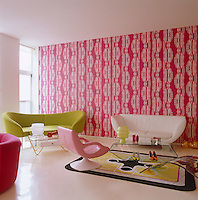 A pair of sofas stand against a backdrop of pink and white wallpaper - all of which are designed by Karim Rashid