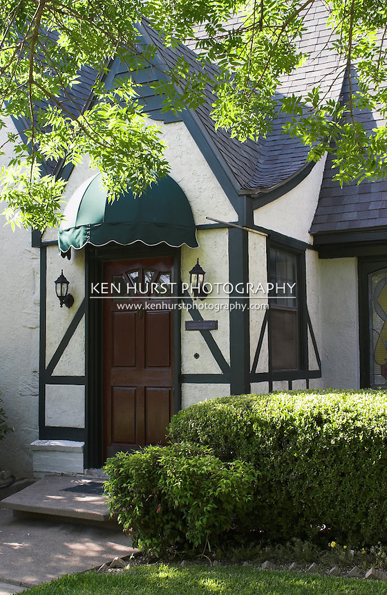 attractive entryway to tudor style house with wood door and green awning; surrounded by foliage and landscaping