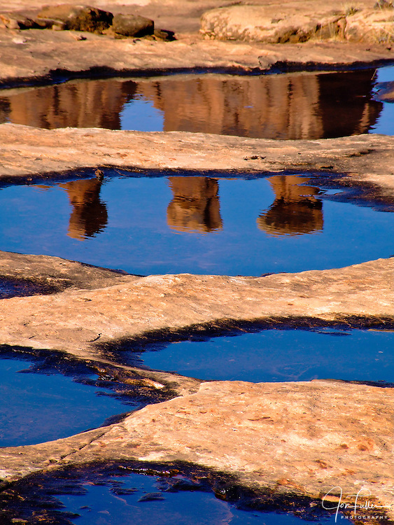 The Three Gossips at Arches National Park near Moab, Utah make a reflection in potholes filled with rain water.