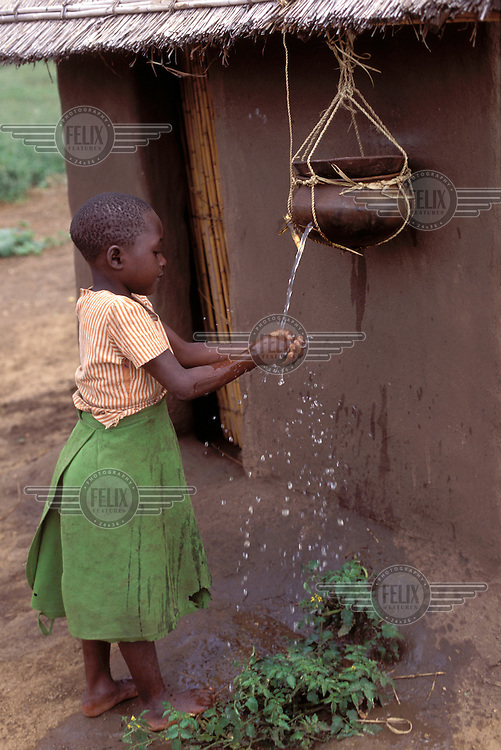 © Giacomo Pirozzi / Panos Pictures..MALAWI..A girl washing her hands outside a latrine.