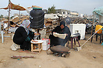 Palestinian women bake bread on firewood outside a tent near the ruins of their houses which witnesses said were destroyed by Israel shelling during a 50-day conflict last summer, east of Khan Younis in the southern Gaza Strip January 27, 2015. The main U.N. aid agency in the Gaza Strip said on Tuesday a lack of international funding had forced it to suspend payments to tens of thousands of Palestinians for repairs to homes damaged in last summer's war. Robert Turner, Gaza director of operations for the United Nations Relief and Works Agency (UNRWA), said in a statement that UNRWA received only $135 million of the $720 million pledged by donors to its cash assistance program for 96,000 refugee families whose homes were damaged or destroyed in the 50-day conflict between the Hamas Islamist movement and Israel. Photo by Abed Rahim Khatib