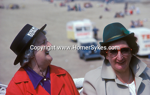"Blackpool Lancasthire  two women on holiday wearing ""Kiss me Quick"" novelty souvenir hats. They are sitting on the pier Please Beach behind."
