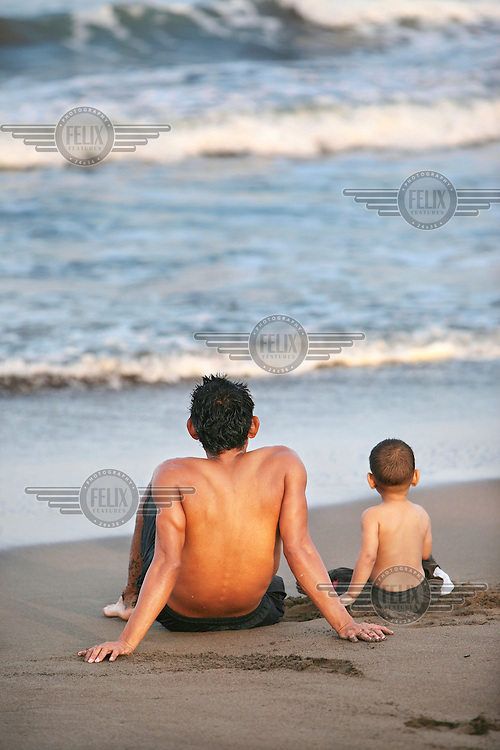 A father and son relaxing on a Caribbean beach near the village Tortuguero.