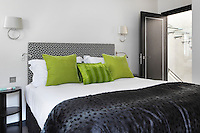 A faux fur throw and lime green velvet cushions give this bedroom a luxurious feel