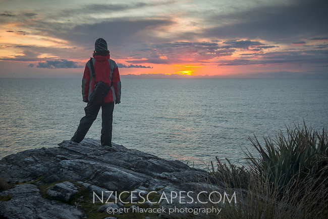 Woman watching sunset on wild coastline at Charleston near Westport, West Coast, New Zealand